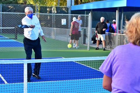 District Commissioner Bob Rollins helps open the Patch Reef Park pickleball courts.